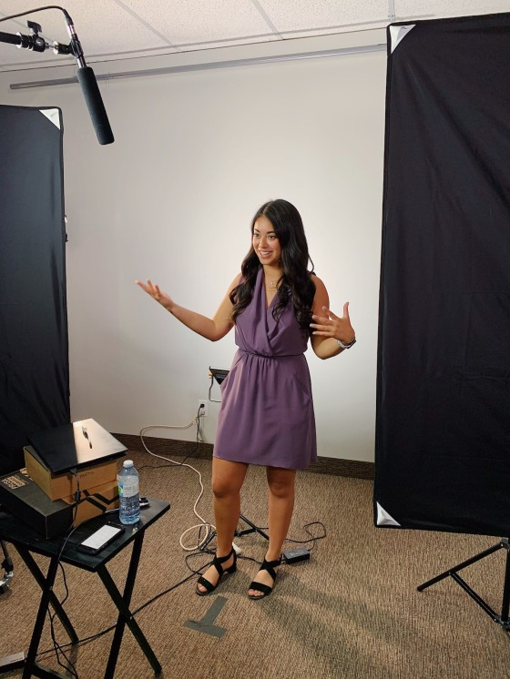 Maite gestures while being filmed in front of a white background and behind production lights
