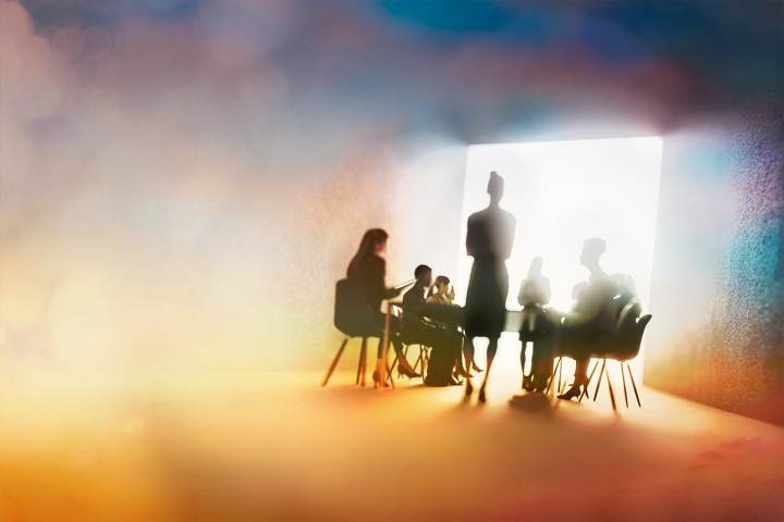 creative silhouette of a shadowed boardroom with a speaker and people sitting in front of them
