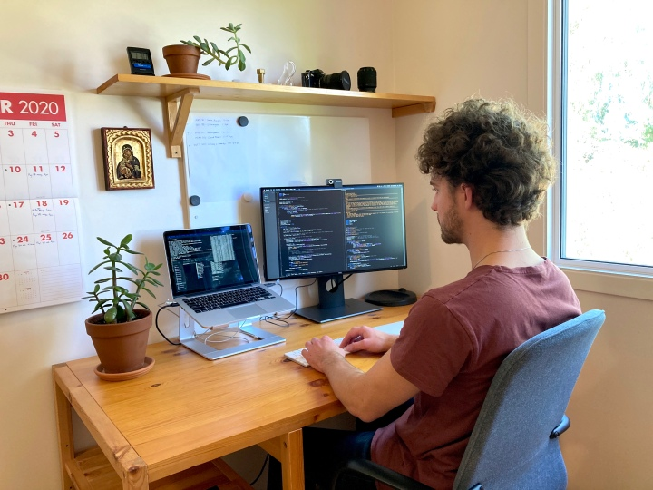 Adam sits at a desk with two screens displaying code in a brightly lit, tidy room.