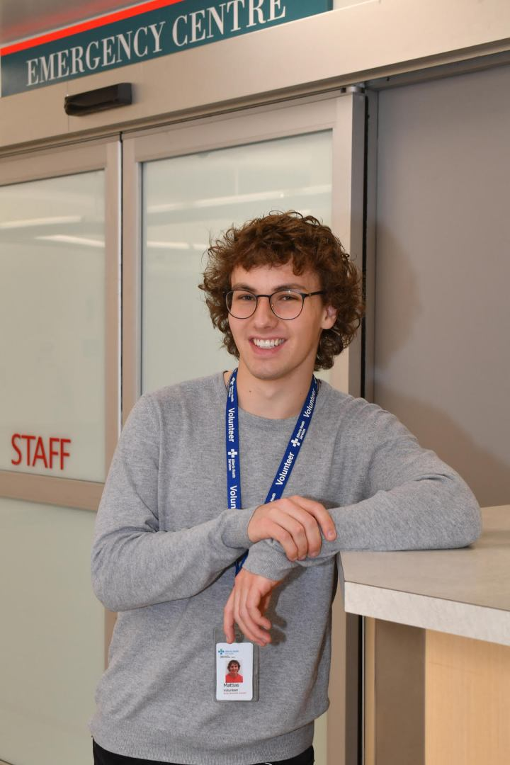 Smiling Mattias poses outside of an Emergency Centre entrance wearing an Alberta Help Services volunteer badge.