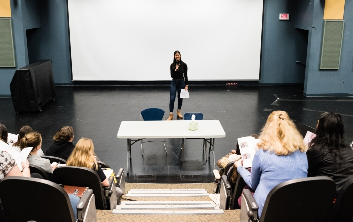 young woman stands on an empty stage and speaks to female audience