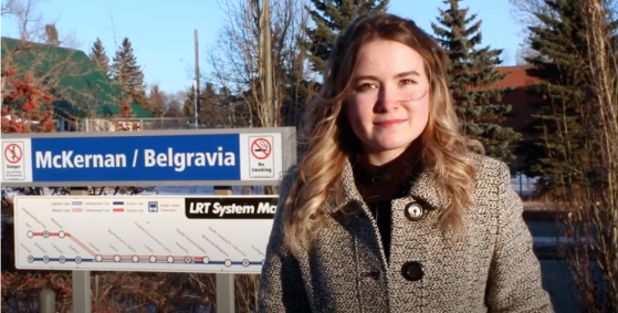 Allie stands in front of the McKernan/Belgravia sign on the Edmonton LRT line.