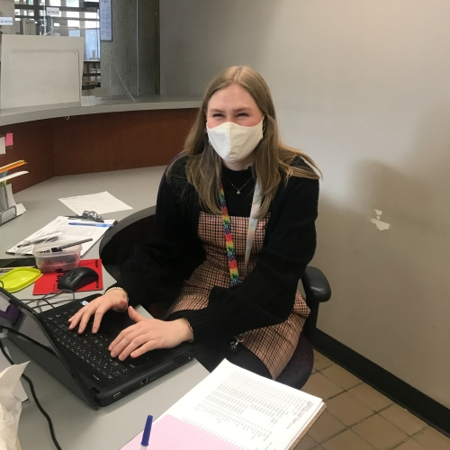 Danielle sits at a desk surrounded by paperwork and is typing on a laptop. She appears to be smiling at the camera even though she's wearing a mask.